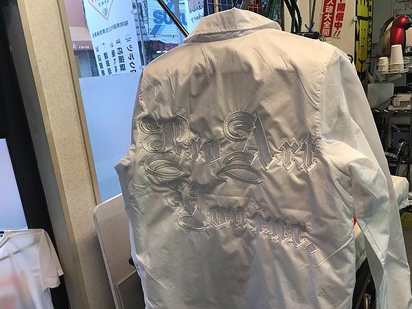 白いジャンパの背中に白糸で刺繍